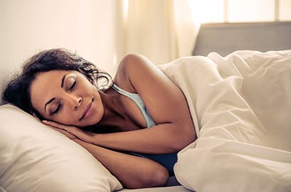 A woman is lying on her side in bed asleep