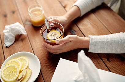 Hands are resting on a table holding a glass mug with a lemon slice in it. Other lemon slices sit on a plate off to the side with a tissue box.