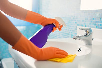 A person wearing gloves is cleaning a bathroom sink