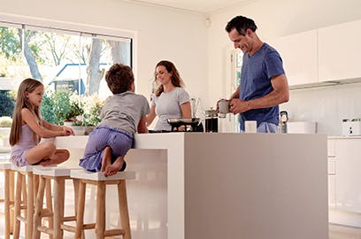 A man and a woman and their 2 children are preparing food together in the kitchen