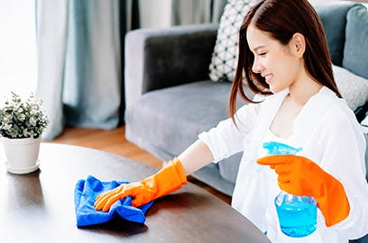 Woman cleaning kitchen table with orange gloves and disinfecting spray