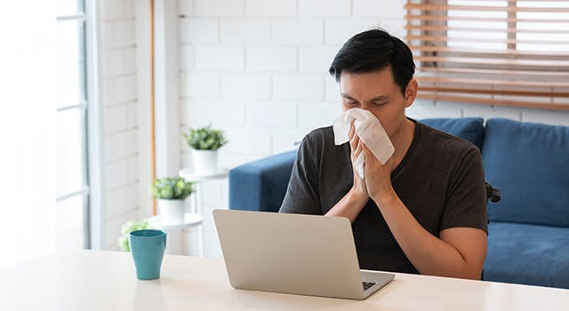 A man is sat at a table with a computer in front of him, blowing his nose