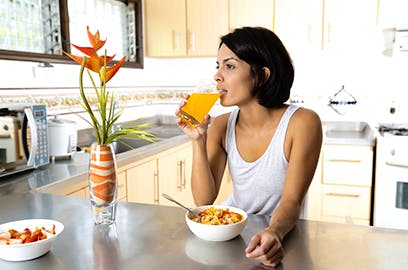 A woman is sitting at a kitchen counter top, she is drinking a glass of orange juice and there is a bowl of cereal in front of her