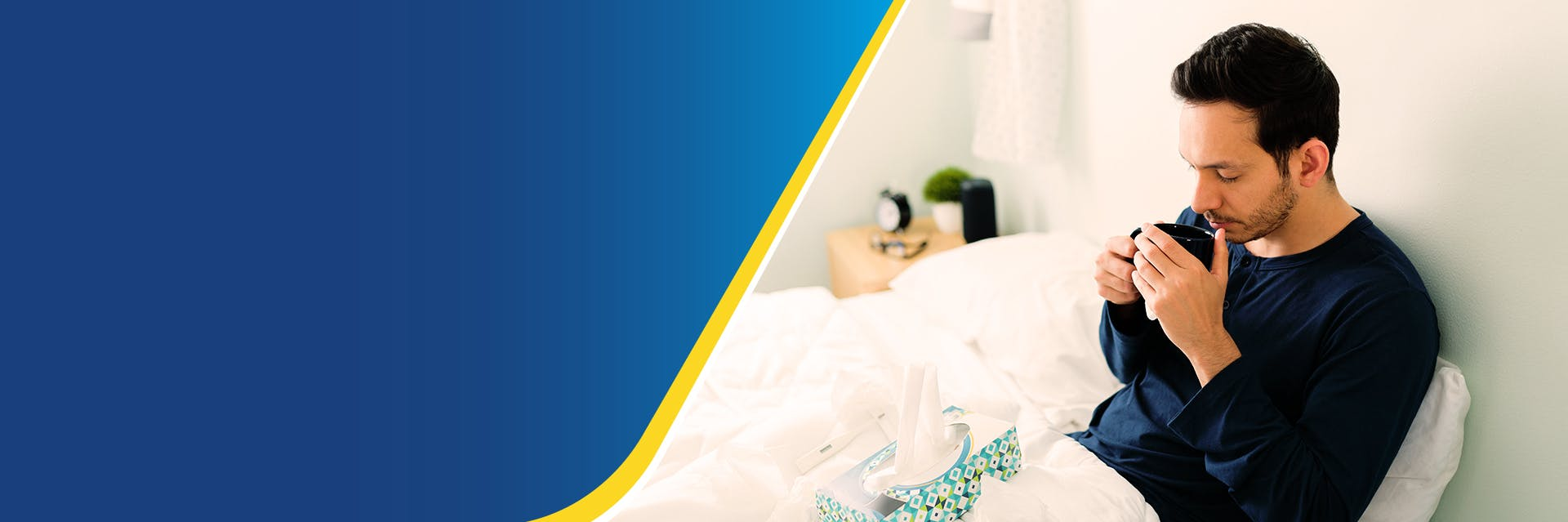 A man is sitting up in bed with a mug and a box of tissues