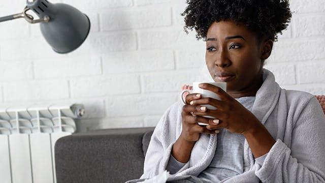 Woman in bath robe holding mug of hot liquid