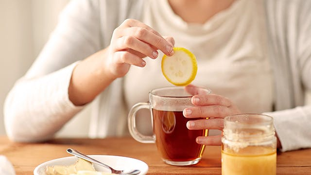 A woman is sitting at a table and adding a slice of lemon to a cup of tea. A plate of lemon and ginger slices and a pot of honey are also on the table.}