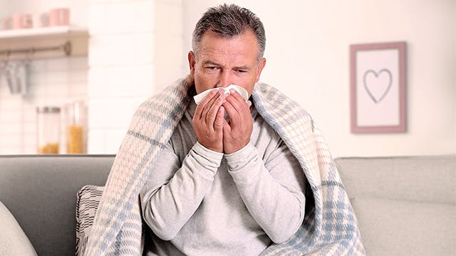 A man is sitting on the sofa under a blanket blowing his nose