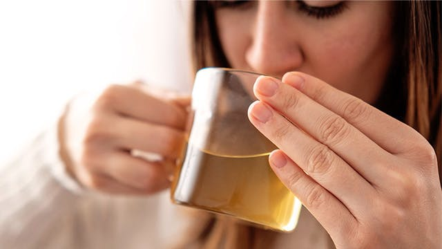 A close up of a woman drinking green tea from a glass mug