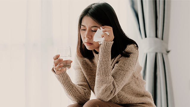 A woman looking tired is sitting and holding a glass of water