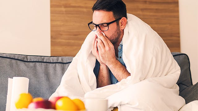 A man wrapped in a duvet is sitting on a sofa, blowing his nose