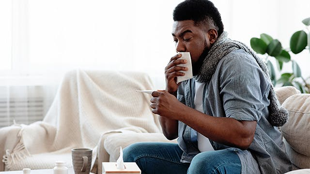 A man is sat on the sofa coughing into a tissue and looking at a thermometer