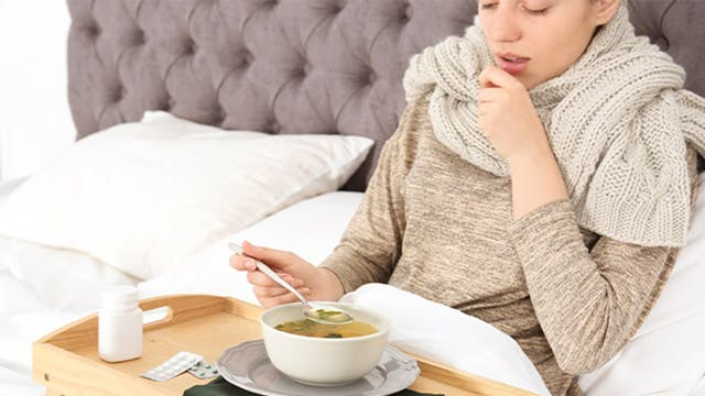 Young sick woman lying in bed eating broth off of a bed tray