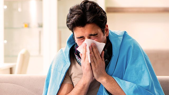 A man is sitting on the sofa wrapped in a blanket and holding a tissue to his face as if he is blowing his nose