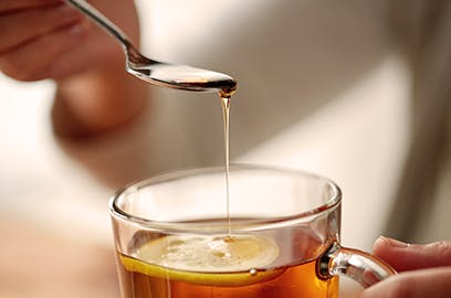 A close up of honey being drizzled into a mug of tea with a lemon slice