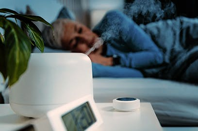 A woman is lying in bed in a darkened room. In the foreground is a humidifier.