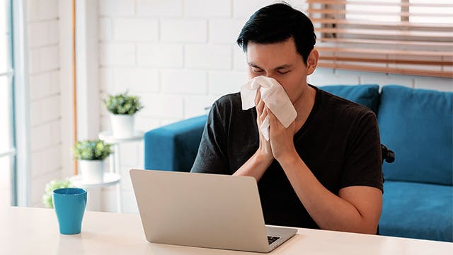 Young man sitting at a desk blowing his nose