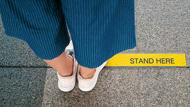 Person wearing blue pants and white shoes standing behind a yellow line on the sidewalk