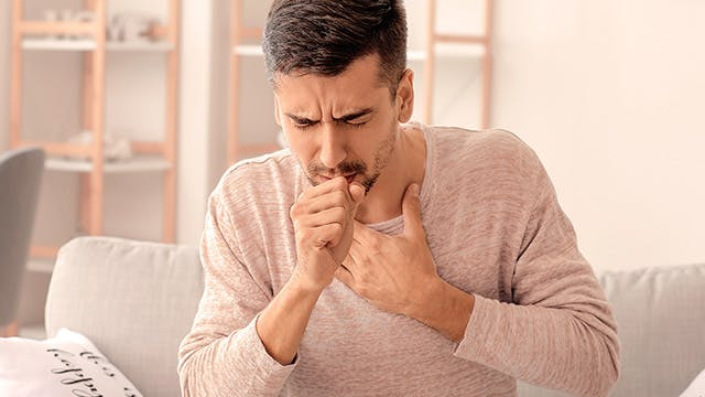 A man is sitting on a sofa and coughing