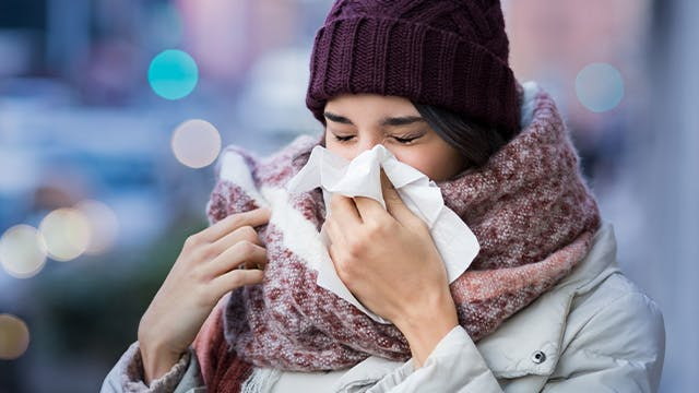 Woman sneezing into tissue holding a mug