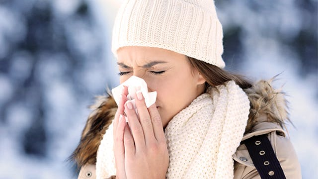 Woman sneezing in the winter