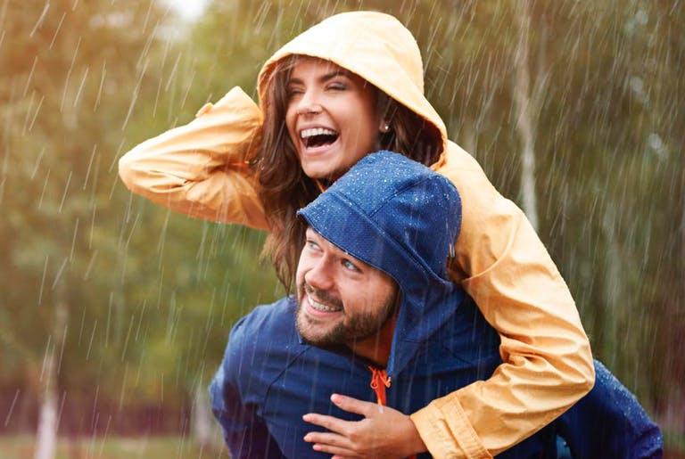 Frau lacht im Regen, getragen von einem Mann