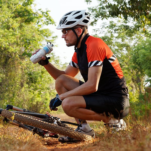 Man drinking water while crouching  near bicycle