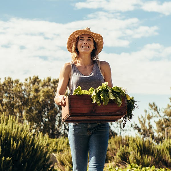 Woman holding basket of green produce