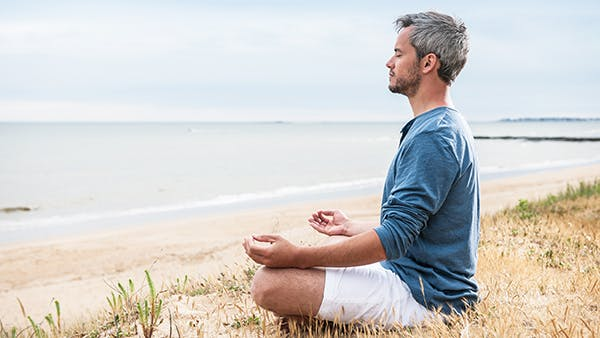 Man sitting on a beach meditating