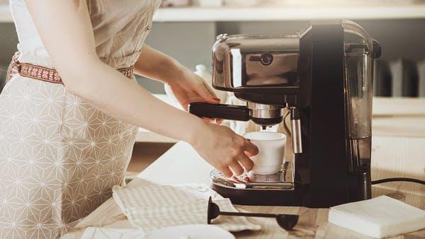 Woman making fresh espresso in coffee maker
