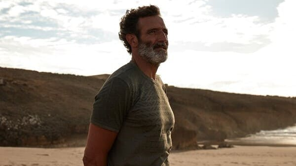 middle aged man with grey beard wearing a t shirt on a beach