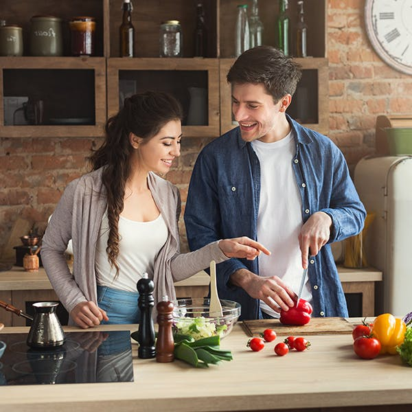 Couple cooking food together on purple background