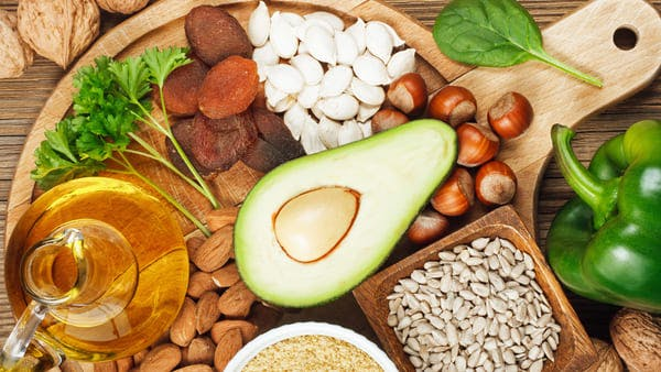 avocado, sunflower seeds, hazelnuts, and other foods rich in vitamin e on wooden plat
