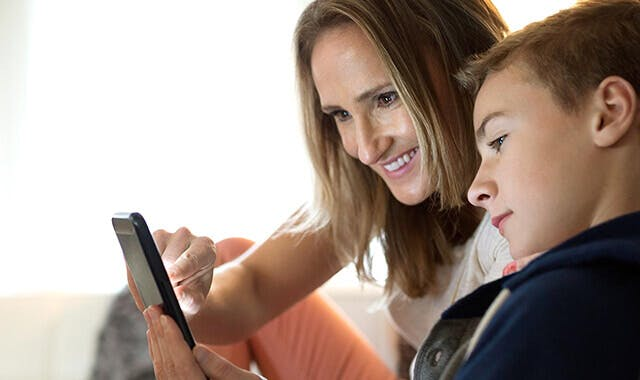 women and child looking at a phone