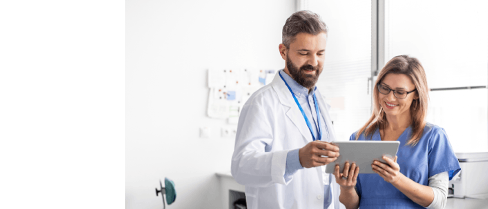 A doctor and a nurse reading something on a tablet