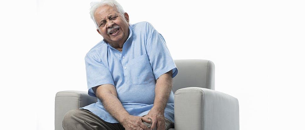 Man clutching knee in pain