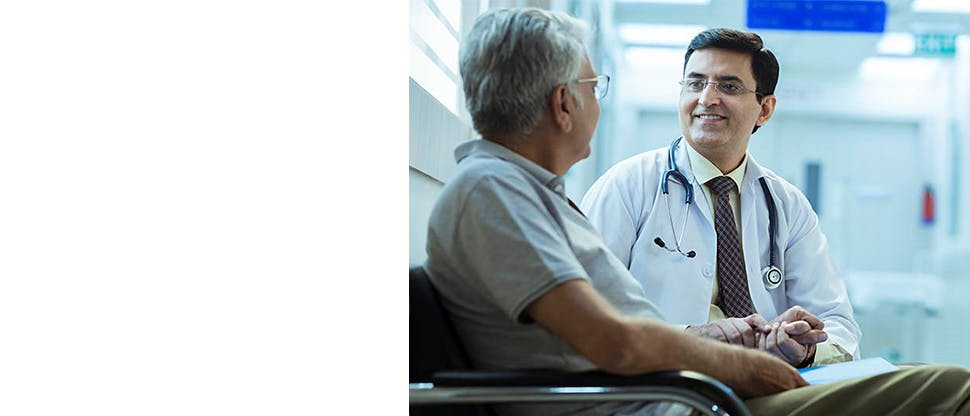 A doctor wearing a stethoscope around his neck talking to an older man by holding his hand