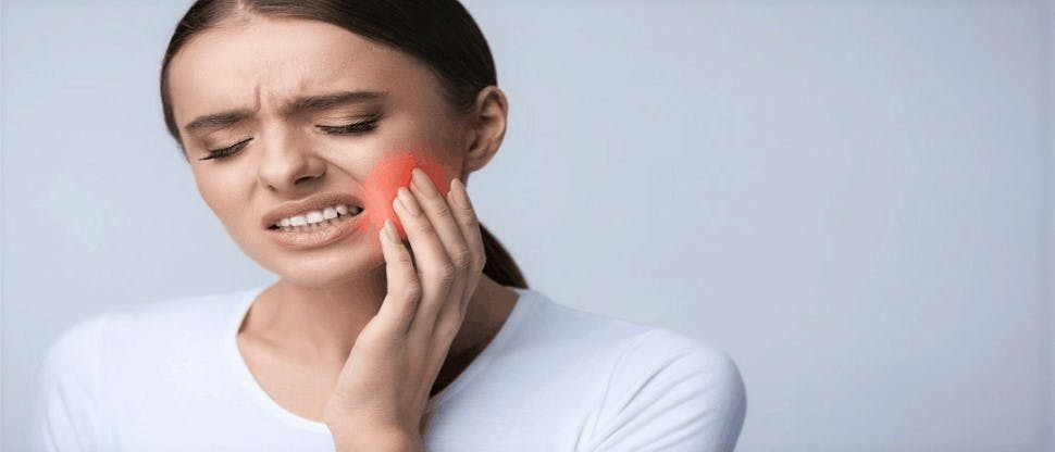 Women holding the side of her cheek by her jaw inpain