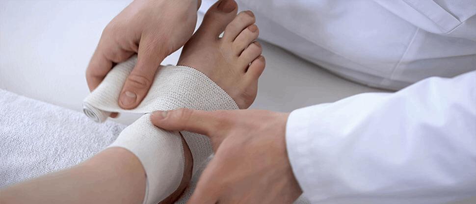 Traumatologist applying bandage to sprained ankle