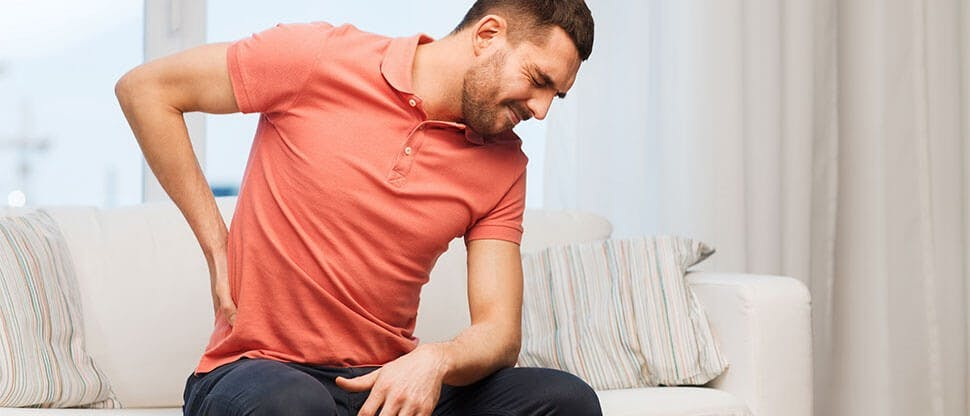 Man on couch suffering from back pain