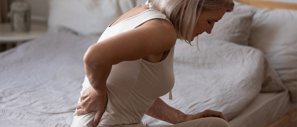 Woman on bed experiencing back pain