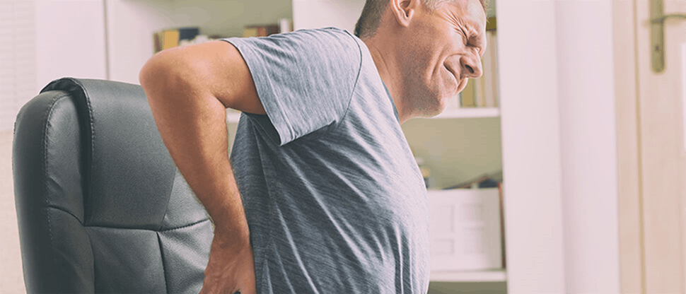 Man suffering from lower back pain in office chair