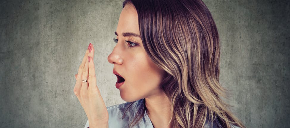 Woman using her hand to test her breath
