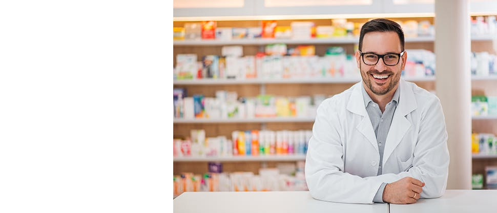 Smiling doctor wearing white coat standing in front of medicine shelf