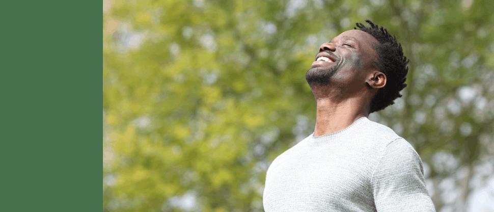 Smiling man facing sunshine