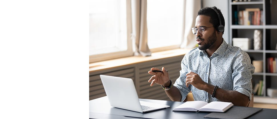 A man wearing headphones taking an online call on a laptop