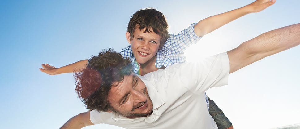 Man playing with son on his back
