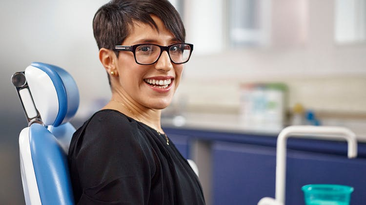 Paciente com óculos a sorrir para a câmara