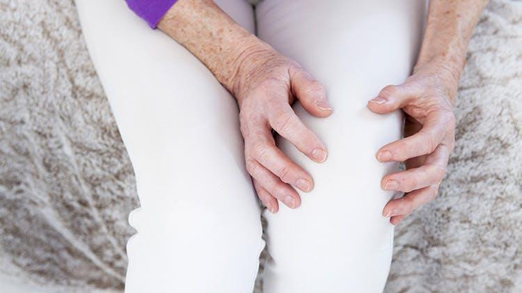 Femeie strângându-se de genunchi