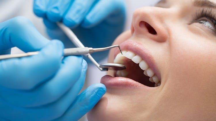 Pacient căruia i se efectuează un examen dentar.