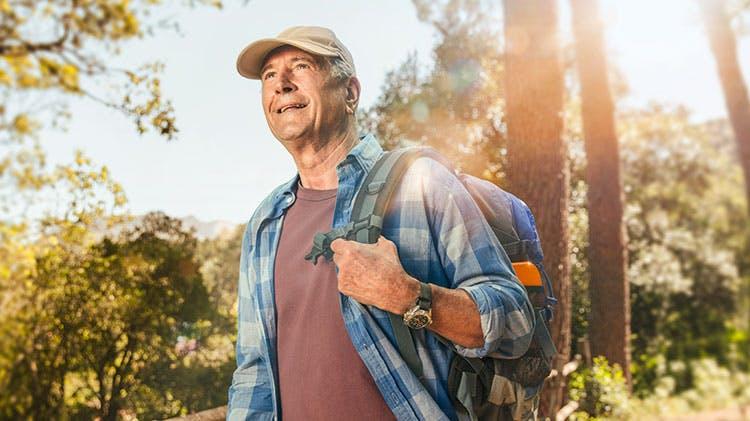 Пожилой человек, гуляющий по лесу